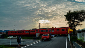 The red train running under the sunbeam before sunset. During the train coming, the cars and people are waiting for the train pass Stock Image