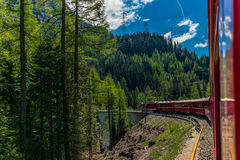 Red train slowly climbing to the Bernina Pass in the Swiss Alps Royalty Free Stock Photos