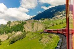 Red train slowly climbing to the Bernina Pass in the Swiss Alps Stock Photos