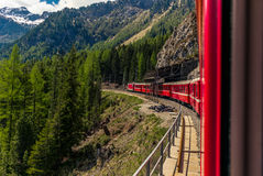 Red train slowly climbing to the Bernina Pass in the Swiss Alps Stock Images