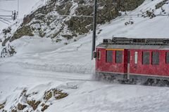 Red train in the snow in swiss alps. Red train running in the snow in swiss alps in winter Royalty Free Stock Images