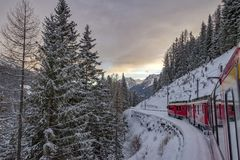 Red train in the snow in swiss alps. Red train running in the snow in swiss alps in winter Stock Photo