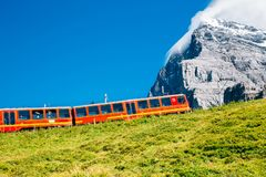Red train and snowy mountain on meadow at Jungfrau region in Switzerland stock photo