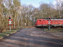 Red train speeding through a level crossing Stock Images