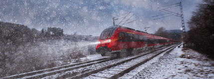 Red train speeding in the snow Royalty Free Stock Image