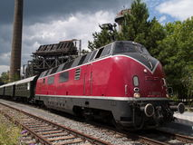 Red train on the tracks. A red train on the tracks pulling cars Stock Image