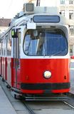 Red tram carries passengers for European cities Stock Photos