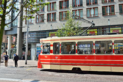 Red tram moves by street in center of Hague. Royalty Free Stock Photography