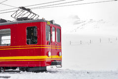 Red tram parks at the hill on snowing day Royalty Free Stock Images