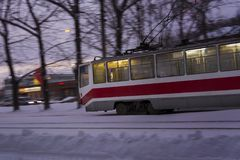 Red tram is passing by with motion blur in a snowy environment. Red street tram on white snow at evening with motion blur. Winter image. Winter evening. Moving stock photos