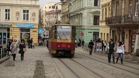 Red tram and people near the Market Square in Lviv, Western Ukraine. UKRAINE, LVIV, APRIL 5, 2015: Red tram and people near the Market Square - is a central stock footage