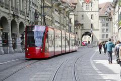 The red tram on a tram rails in Bern. Bern, Switzerland - April 17, 2017: The red tram on the move is on a straight stretch of road in the old town. The tram Royalty Free Stock Photos