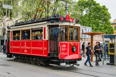 Red tramway on the Istiklal street in Istanbul, Turkey. Istanbul, Turkey - April 08, 2016: People are walking down the Istiklal street near the  red tramway in Royalty Free Stock Photography