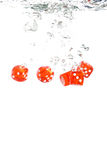 Red transparent dice falling into the water Royalty Free Stock Photography