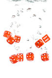 Red transparent dice falling into the water Stock Photo