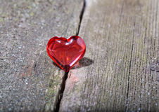 Red transparent glass heart on old gray boards Royalty Free Stock Photography
