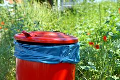 Red trash bin on footpath and a green area. waste bins on curb. stock image