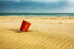 Red trash bin in the sand Royalty Free Stock Photography