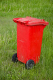 Red trashcan on green summer  resort  grass Royalty Free Stock Photos