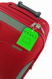 Red travel bag and green tag Royalty Free Stock Images