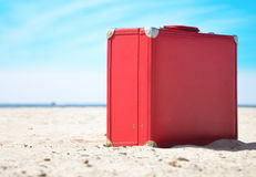 Red Travel Suitcase on Sunny Beach. A red travel suitcase is alone on a beach with the lake or ocean in the background. Use this image to represent a voyage Royalty Free Stock Photography