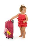 Red traveler baby girl. Baby girl in red dress with traveler bag, looking to the horizon (isolated royalty free stock photo