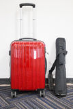 Red travelling suitcase and camera tripod Stock Photography