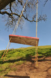 Red tree swing hangs from a large oak branch Stock Images