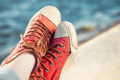 Red trendy sneakers on girl and seascape as background Royalty Free Stock Image