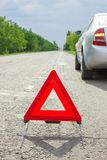 Red triangle of a car on the road. Breakdown of the car in bad weather Stock Photography