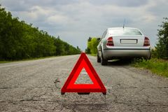 Red triangle of a car on the road. Car warning triangle on the road against the city in the evening. Breakdown of the car in bad w Royalty Free Stock Photo