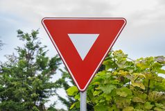 Red triangle road traffic coordination sign. With bush city background close Royalty Free Stock Photography