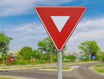 Red triangle road traffic coordination sign on road. On the city road background Royalty Free Stock Image