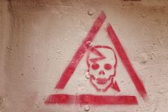 Red triangle with a skull. Danger sign painted on the wall.  stock photos