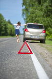 Red triangle warning sign and broken car on the road Stock Image