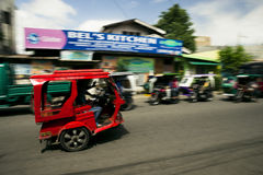 Red tricycle. Kalibo, Philippines - February 10, 2016. Red tricycle and the driver waving his hand to the camera Royalty Free Stock Image