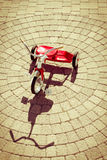 Red Tricycle with Shadow on Sunny Stone Patio Royalty Free Stock Images