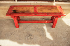 Red trimmed wood bench. Weathered wood bench painted red stock photography