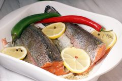 Red trout fish, ready to be baked in the oven with lemon and hot pepper in a white heat-resistant dish.  stock photo