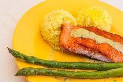 Red trout steak fillet with rice and asparagus on a yellow plate stock photos