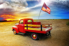 Red Truck. Red vintage pick up truck with American flag in wide open country side with dramatic sunset cloudscape stock photo