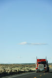 Red truck, american highway, blue sky. A red truck moving on an interstate highway of USA , the road runs through the plain, in bright blue sky and little white Stock Photography