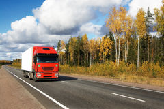 Red truck on autumn highway Stock Photo