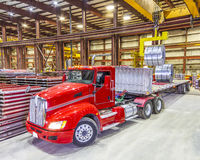 Red truck being loaded in the bay under ceiling lights. Red semi tractor trailer truck being loaded with roll formed steel coils - inside bay lit up with ceiling Royalty Free Stock Images