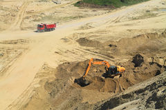 Red truck and excavator in a quarry in sunny day. POLEWOJE, KALININGRAD REGION, RUSSIA — JUNE 18, 2014: Red truck and excavator in a quarry in sunny day Royalty Free Stock Photography