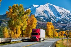 Red truck on highway in Colorado at autumn. USA. Mount Sopris landscape royalty free stock photography