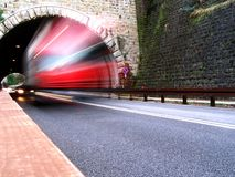 A red truck leaving a tunnel stock image