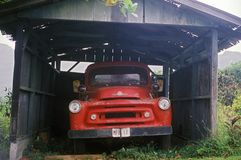 A red truck under an old carport in Hawaii Stock Photos
