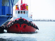 Red Tug Boat. In the sea near big vessel stock images