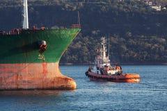 Red tug goes near bow of big cargo ship Stock Photos